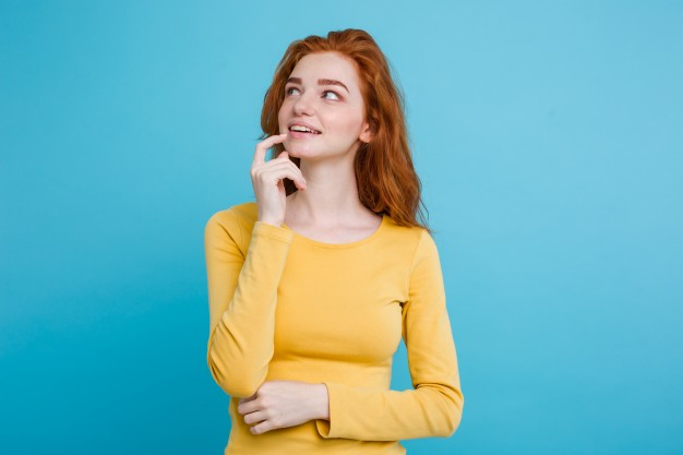 portrait-of-happy-ginger-red-hair-girl-with-freckles-smiling-looking-at-camera-pastel-blue-background-copy-space_1258-782