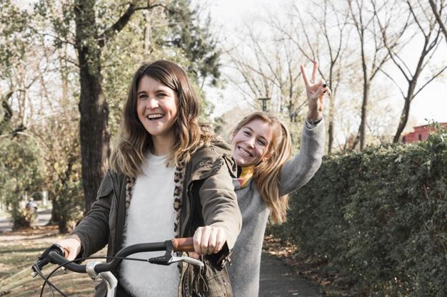 women-riding-bike-in-park_23-2147935721